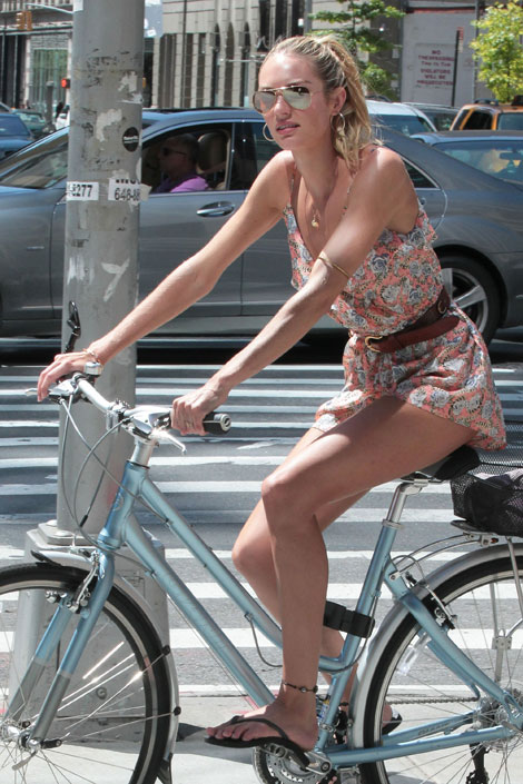 Candice Swanepoel in short jumpsuit riding her bike